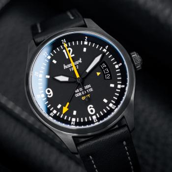 Hanhart S-Serie SK 60 GMT: Ambiente Ansicht der Uhr in schwarz aus Edelstahl mit weißen und gelben Zeigern und schwarzem Lederarmband